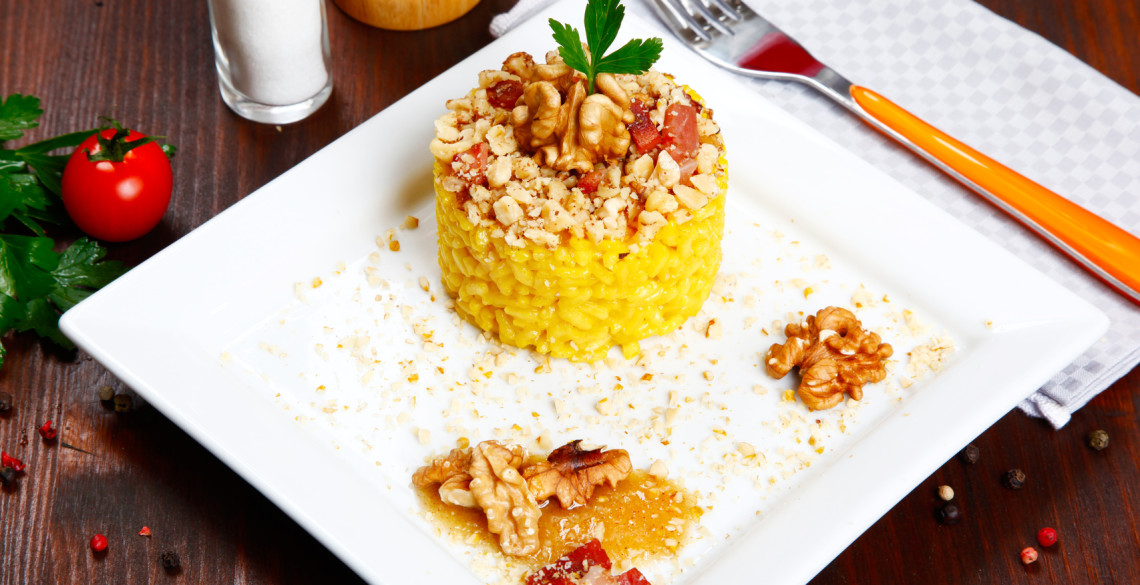risotto with walnuts, saffron, speck on a dish